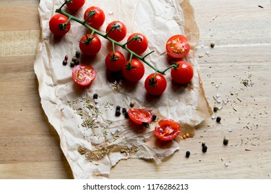 Red Food cherry tomatoes on brown paper wooden chopping board, rustic image