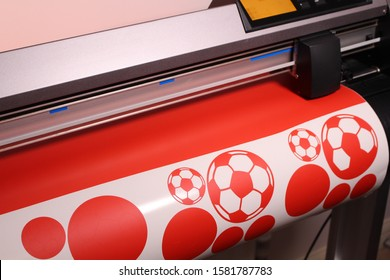 Red Footballs being produced on a Vinyl Cutter using Red Vinyl