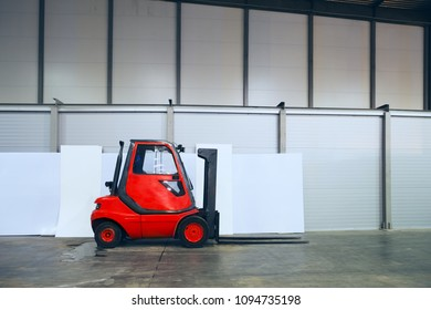 red forklift truck on a large empty warehouse
