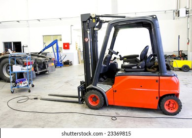 Red forklift vehicle in truck service garage