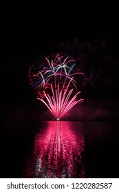 Red fountain and color sparkles from rich fireworks over Brno's Dam with lake reflection