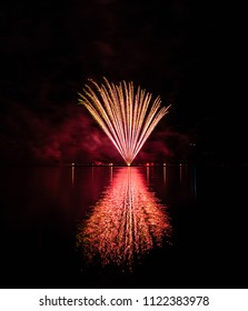 Red fountain fireworks over Brno's Dam with great lake reflection