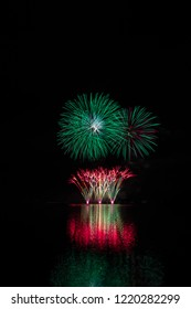 Red fountain and green starts from rich fireworks over Brno's Dam with lake reflection