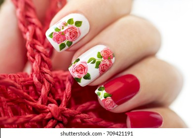 Red French manicure with design of roses on a white background.Nail art.