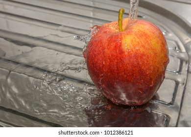 Red fresh apple with water - wash fruit with water - splashing clear water