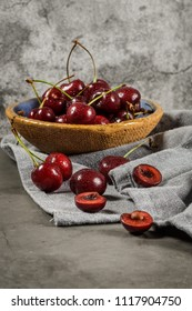 Red fresh cherries in bowls and a bunch of cherries on the table.
