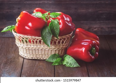 red fresh paprika peppers and green leaves in a wicker basket close-up. fresh red paprika on wooden background. background with paprika.