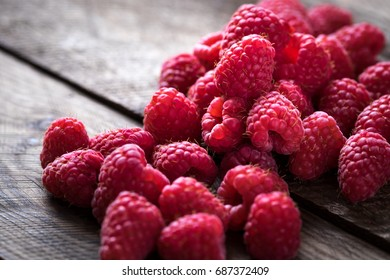 Red fresh raspberries on a wooden background