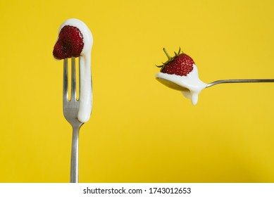 Red fresh strawberry on the fork and spoon with white sweet cream