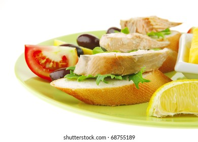 red fried salmon chunks on baguette slices