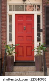 Red Front Door in White Door Frame with Windows and Plants