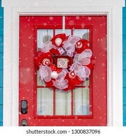 Red front door with wreath viewed on a snowy day