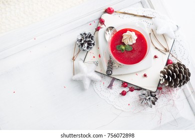red fruit Panacotta with green mint leaves over Christmas background