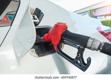 Red fuel nozzle in pouring to white car, Thai Petrol pump filling nozzles , Gas station in a service, Refueling Vehicle With Gasoline Nozzle, Bangkok Thailand