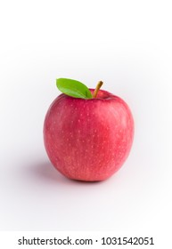 A red Fuji apple with leaves