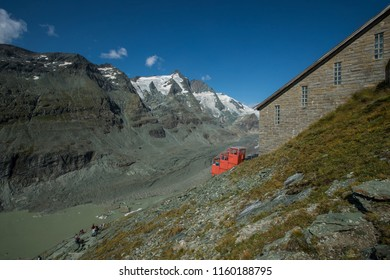 Red funicular on the Grossglockner mountain range, just behind the Pasterze glacier in the background on a warm sunny day with blue skies in the summer of 2018