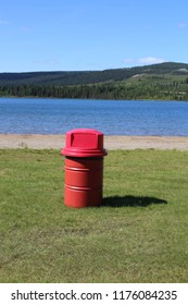 Red garbage Can at park with green grass and blue water