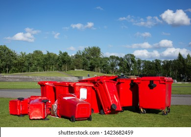 Red garbage containers on the green grass on the background of blue sky