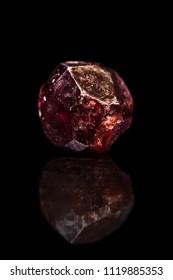 Red garnet gemstone, silicate minerals, black background with reflection