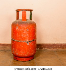 Red gas cylinder on pink wall background