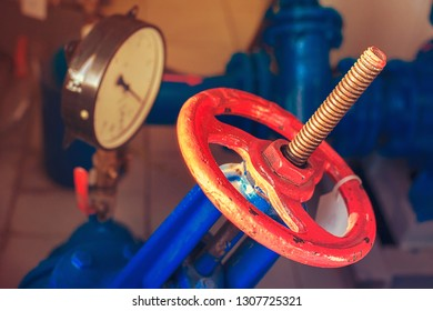 Red gas valve and pressure gauge with an arrow on the limit. Background for gasification.