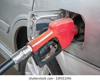 Red gasoline nozzle filling up a car