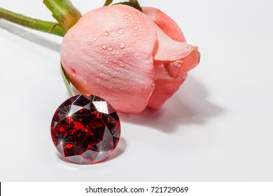 The red gemstones shine light pendant in front of pink rose flower.