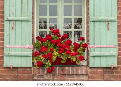 Red Geraniums Blooming in Flower Boxes Outside of Window  and Green Wooden Shutters on Brick Building in Europe, France.