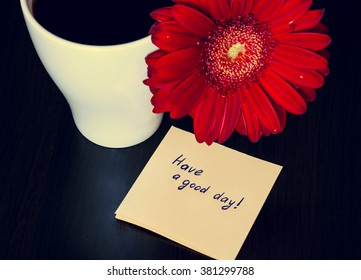 """Red gerbera flower, cup of coffee and paper with text ''Have a good day!"""" on the wooden desk. Selective focus, toned"""
