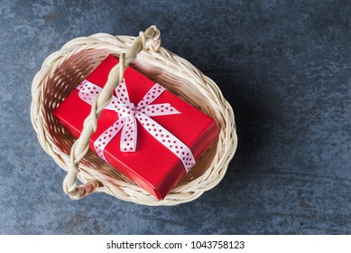 Red gift box in basket over dark stone background.