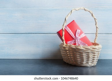 Red gift box in basket over blue wooden background.