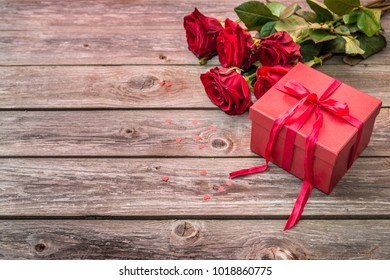 red gift box with bow and bouquet of red roses on wood background. Valentines Day background