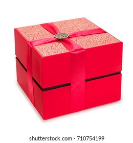 Red gift box with Chinese pin ornament for Happiness on top of a ribbon. Isolated on White Background.