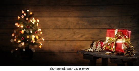red gift box and christmas decoration on an old stool, blurry tree with lights in the background against a rustic wooden wall, copy space, panoramic format, selected focus