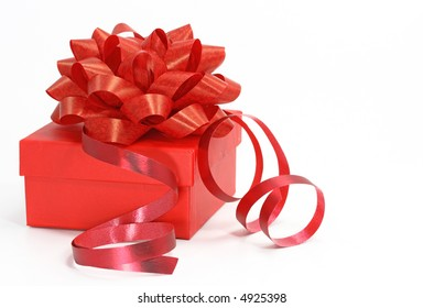 red gift box with a curly ribbon on white background