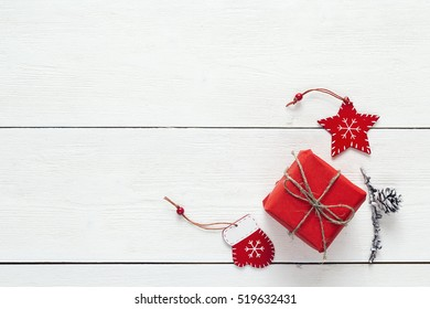 Red gift box with decoration and pine cone on a white wooden table. Christmas background. Space for text. Top view.