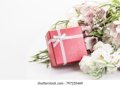 red gift box and flowers on white