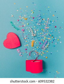 Red gift box in form of heart with various party confetti, streamers, noisemakers and decoration on a blue background. Colorful celebration concept.