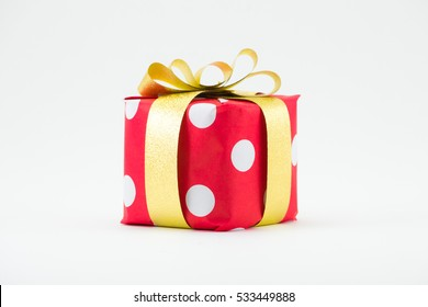 Red gift box with gold ribbon isolated on white background.