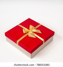 red gift box with gold ribbon bow, isolated on white.