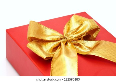 Red gift box with golden ribbon knot close-up.