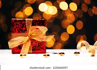 Red gift box with golden ribbon over black backdrop with christmas lights. Front view.