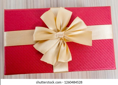 Red Gift Box With the golden Ribbon on the wooden table