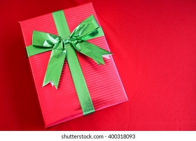 red gift box with green ribbon on red background