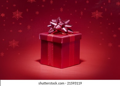 Red gift box on red background with snowfall