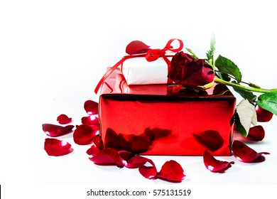 Red gift box on a bright red rose petals on a white background V