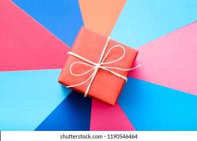 red gift box on colorful background. present as a reward and gratitude on special occasion.