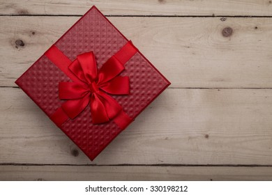 Red gift box on vintage wooden background