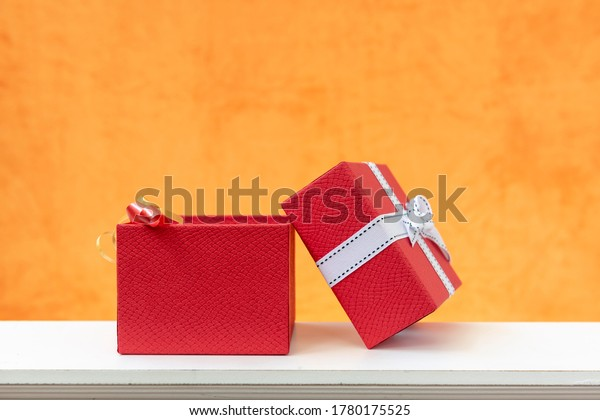 Red gift box with open lid, on orange background