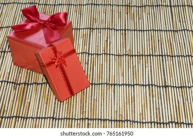 Red gift box is perfect for celebrating Christmas on bamboo floor.